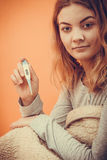 Sick woman under blanket with digital thermometer. Royalty Free Stock Photos