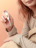 Sick woman under blanket with digital thermometer. Stock Images
