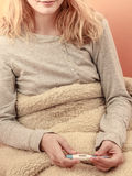 Sick woman under blanket with digital thermometer. Royalty Free Stock Photography