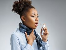 Sick woman using spray for throat. Photo of african american woman in blue shirt suffering virus of flu on gray background. Medical concept royalty free stock photo