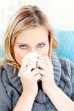 Sick woman using a tissue sitting on a sofa Royalty Free Stock Photos