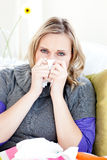 Sick woman using a tissue sitting on a sofa Stock Image