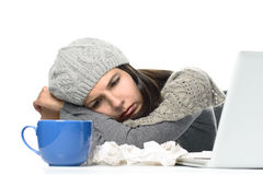 Sick Woman in Winter Attire with Laptop and tea Stock Photo