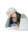 Sick Woman in Winter Attire with Laptop and tea. Close up Tired Sick Woman in Gray Winter Attire Working with Her Laptop While Having Cup of hot tea on Desk Royalty Free Stock Photos