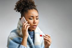 Sick woman wrapped in blanket with a high temperature calling on the phone. Photo of african american woman suffering cold and winter flu virus on gray royalty free stock images