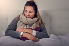 Sick woman wrapped in a warm scarf and clutching a hot water bottle. Sitting using nasal spray with a miserable expression in a seasonal healthcare or flu Stock Photos