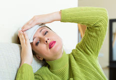 Sick  woman. Sick young  woman with huge migraine holding wet towel on her head Stock Photography