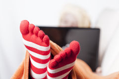 Sick women in funny toesocks on couch Royalty Free Stock Images