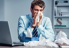 Sick worker blow his nose in paper tissues. Photo of young man working in the office. Business concept stock photos