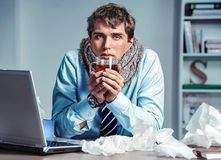 Sick worker has high temperature. Bad feeling. Sick worker has high temperature. Photo of young man in office suffering virus of flu. Medical concept royalty free stock photography
