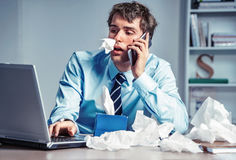 Sick worker with paper tissues on the desk, talking on the phone. Photo of young man working in the office. Business concept royalty free stock image