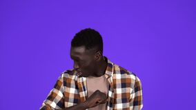 Sick young African Man coughing hard and hitting himself the chest isolated on blue background. Wearing plaid shirt