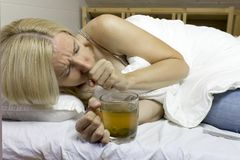 Sick young blond woman holding a cup of green tea and coughing on the couch stock photography