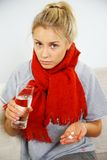 Sick young blond woman with pills Stock Photos