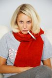 Sick young blond woman with thermometer Royalty Free Stock Image