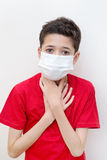 Sick young boy clutches his throat with face mask on. Royalty Free Stock Image