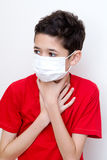 Sick young boy clutches his throat with face mask on. Stock Photography