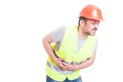 Sick young builder suffering and holding his tummy. As indigestion concept isolated on white with copyspace royalty free stock images
