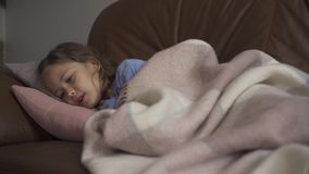 Sick young caucasian girl coughing while lying under blanket at home. The child has fever. Concept of health, illness. Sick young caucasian girl coughing while stock video footage