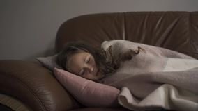 Sick young caucasian girl coughing while lying under blanket at home. The child has fever. Concept of health, illness. Sick young caucasian girl coughing while stock video