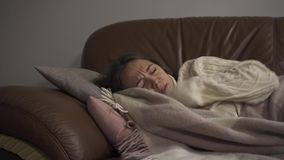 Sick young caucasian girl at home. The woman has fever. Concept of health, illness, sickness, common cold, treatment. Sick young caucasian woman lying under stock video