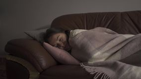 Sick young caucasian girl with dark circles under her eyes lying under blanket at home. The woman has fever. Concept of. Sick young caucasian woman with dark stock video