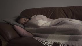 Sick young caucasian woman with dark circles under her eyes lying under blanket at home. The woman has fever. Concept of. Sick young caucasian woman with dark stock video