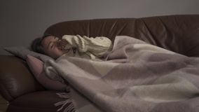 Sick young caucasian girl lying under blanket at home. The woman has fever. Concept of health, illness, sickness, common. Sick young caucasian woman lying under stock video footage