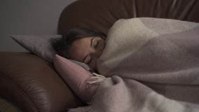 Sick young caucasian girl lying under blanket at home. The woman has fever. Concept of health, illness, sickness, common. Sick young caucasian woman lying under stock video