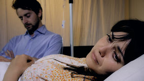 Sick young depressed woman  in hospital with husband sleeping in chair next to her. Man reading while waiting in hospital next to sick woman Stock Images