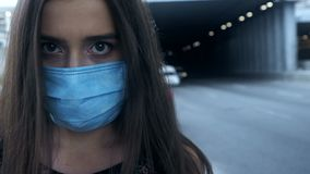 Sick young female putting safety mask on, big city pollution, epidemic virus