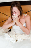 Sick young girl. A sick young lady in bed, blowing her nose and with a pile of tissues lying in front of her Stock Photo