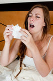 Sick young girl. A sick young lady in bed, holding a tissue in front of her face to stop a sneeze Stock Photo