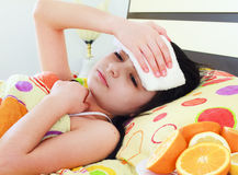 Sick young girl in bed. With fever stock photos