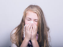 Sick young girl blowing her nose with paper tissue Royalty Free Stock Photos