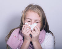 Sick young girl blowing her nose with paper tissue.  Stock Images