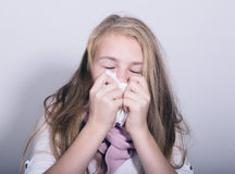 Sick young girl blowing her nose with paper tissue Stock Photos