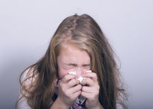 Sick young girl blowing her nose with paper tissue.  Royalty Free Stock Image