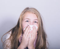 Sick young girl blowing her nose with paper tissue.  Royalty Free Stock Photography