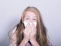 Sick young girl blowing her nose with paper tissue.  Stock Photos