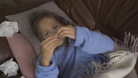 Sick young girl measuring body temperature with a thermometer while lying under blanket at home. The child has fever. Sick young caucasian girl measuring body stock video