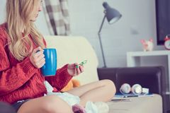 Sick young girl with pills and cup of tea sitting on the sofa. stock photography