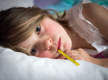 Sick young girl. With a thermometer Royalty Free Stock Photo