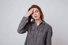 Sick young lady with headache touching her head. Image of sick young lady with headache dressed in shirt standing isolated over gray background and touching her Stock Image