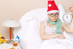 Sick young lady in her bed. During new years day celebration Royalty Free Stock Photography