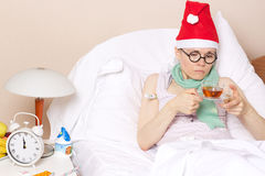 Sick young lady in her bed. During new years day celebration Stock Image