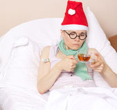 Sick young lady in her bed. During new years day celebration Royalty Free Stock Images
