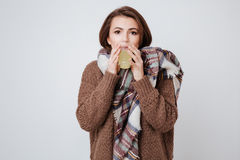Sick young lady holding glass with medicine. Sick young lady in sweater and scarf holding glass with medicine and looking at camera.  gray background Stock Photo