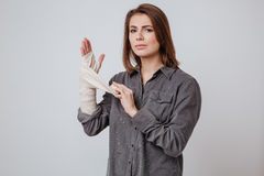 Sick young lady with the plaster on hand. Picture of sick young lady with the plaster on hand dressed in shirt standing  over gray background Royalty Free Stock Images