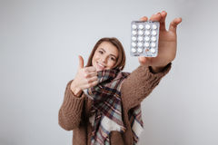 Sick young lady showing to camera medicine pills. Photo of sick young lady in sweater and scarf showing to camera medicine pills. Isolated over gray background Royalty Free Stock Image